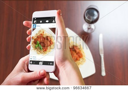 Hand holding smartphone against overhead view of spaghetti and meatballs with basil leaf