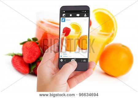 Female hand holding a smartphone against strawberry smoothie and orange juice