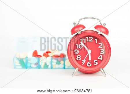 Red Alarm Clock And Medicine In Weekly Pill Box