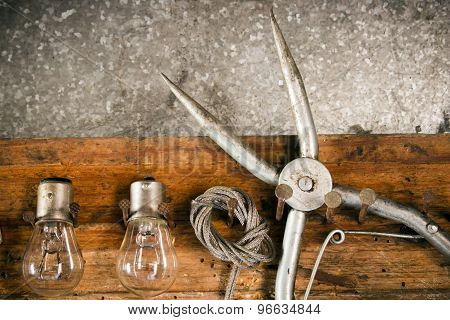 Pliers, Bulbs, Rope, Key, Hanging On Nails On The Old Wooden Stand Close Up