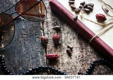 Glasses, Beads, Books, Nuts, Rose Hips On A Wooden Background Closeup