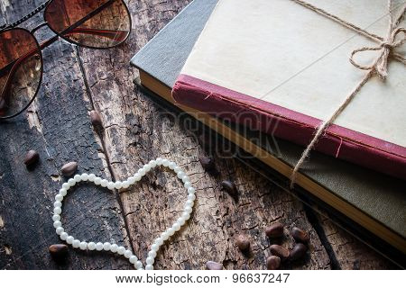 Glasses Tied With A Rope In A Book With Heart-shaped Beads And Pine Nuts