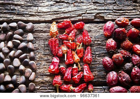 The Figure Of The Pine Nuts, Dry Red Peppers And Dogrose On Wooden Background Close-up