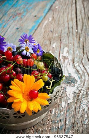 Half Of The Plate With The Leaves And Berries Of Black And Red Currant With A Flower On A Wooden Bac
