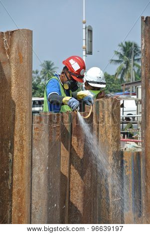 Construction workers sraying the anti termite chemical treatment to the pile cap