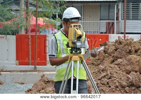 Surveyor using survey equipment at construction site