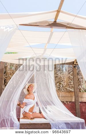 Beautiful young woman at the summer lounge under white veil