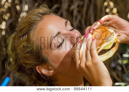 Woman eating a cheese burger at the summer lounge bar