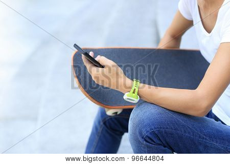closeup of young woman skateboarder use smart phone in city