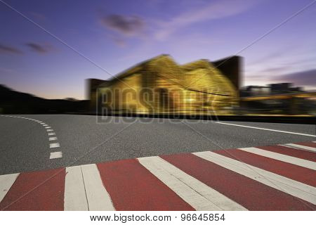 Illuminated modern building exterior and  empty street
