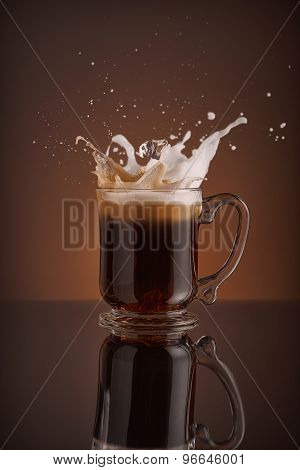 Splash of  ice cappucino drink on a brown background. Refreshing Iced coffee liquid drink pouring i
