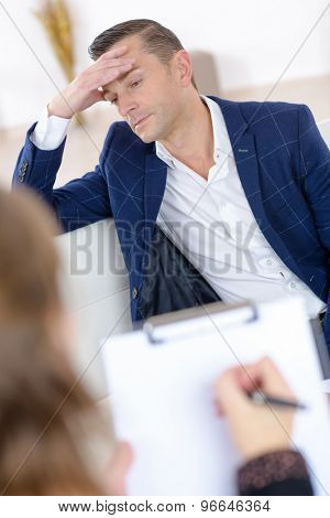 Man looking stressed, woman holding clipboard