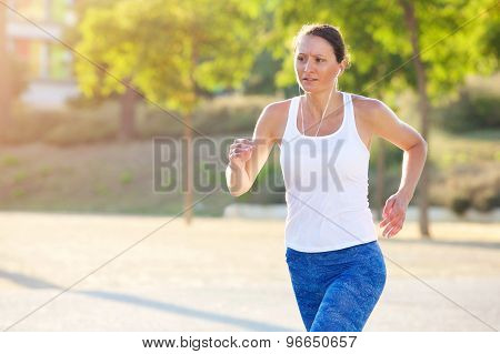 Fit Woman Running With Earphones Outside