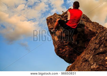 Man climbing on rock.  Young fit, strong male climber