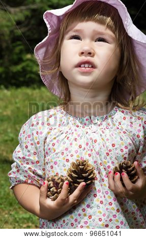 Little girl with pine cones