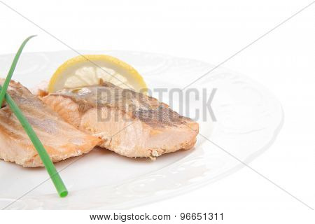 sea food : roasted pink salmon fillet with chinese onion, and lemon on white dish isolated over white background