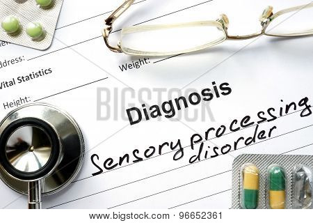 Diagnosis Sensory processing disorder and tablets on a wooden table.