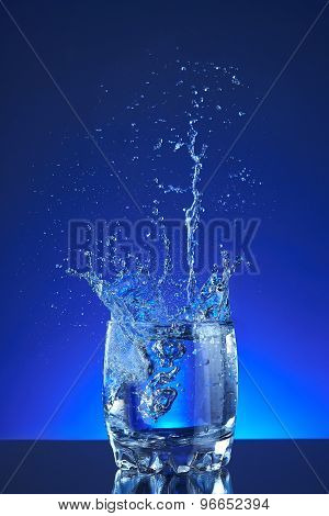 Water splash poured into a glass, blue background, refreshing, freshness and health. Water bottle,