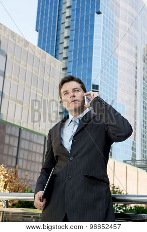 Young Attractive Businessman Talking On Mobile Phone Outdoors
