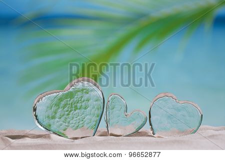 clear glass hearts on white sand beach, ocean,  sky and seascape