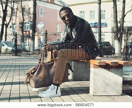 Fashion Elegant Young African Man Wearing A Sunglasses And Black Leather Jacket With Bag Sits On A B