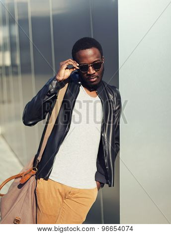 Fashion Portrait Of Elegant Young African Man Wearing A Sunglasses And Black Leather Jacket With Bag