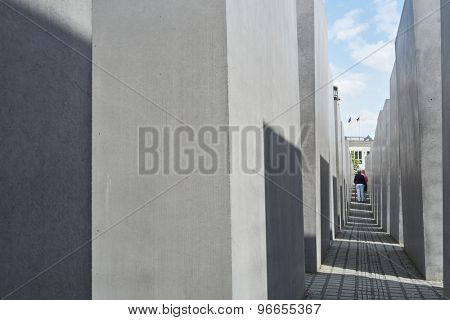 BERLIN, GERMANY - JULY 08: Elderly couple walking among stone blocks at the Memorial to the Murdered Jews of Europe. July 08, 2015 in Berlin.