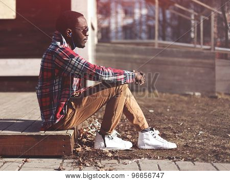 Lifestyle Fashion Portrait Of Stylish Young African Man Listens To Music Evening And Enjoys Sunset,