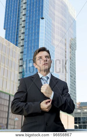 Young Businessman Adjusting Shirt Cuff Link  Outdoors At Exterior Office Building