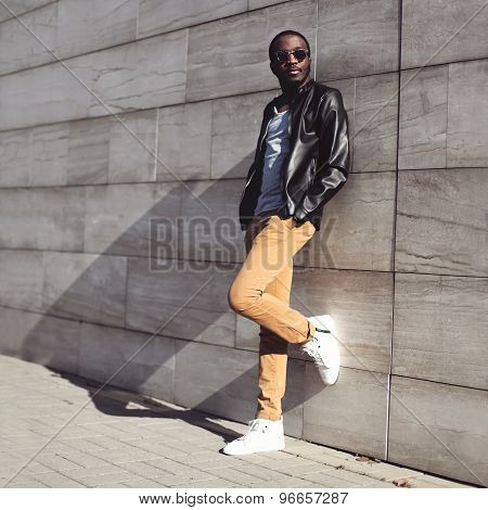 Street Fashion, Stylish Young African Man Wearing A Sunglasses And Black Leather Jacket On Evening C