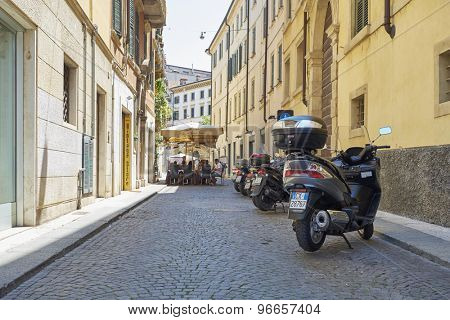 VERONA, ITALY - JULY 11: Low angle shot of stone street with scooters parked. July 11, 2015 in Verona.