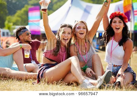 Friends sitting on the grass cheering at a music festival