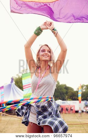 Blonde woman dancing with hula hoop at a music festival, vertical