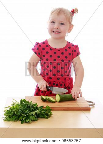 The little girl is cutting vegetables with a knife