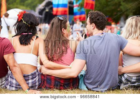 Young people sitting outdoors at a music festival, back view