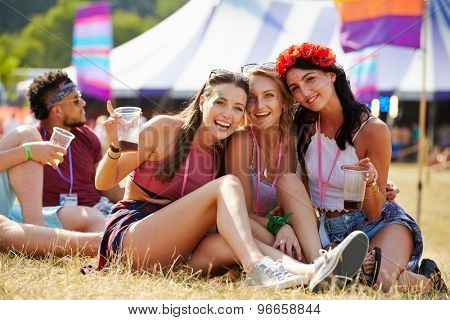 Friends sitting on the grass having fun at a music festival