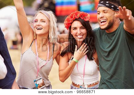 Three friends in the audience at a music festival