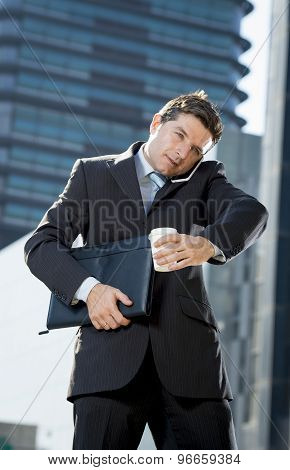 Attractive Businessman Talking On Mobile Phone Outdoors With Coffee And Portfolio