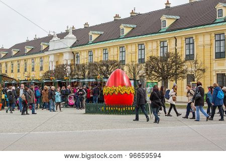 Large Red Egg At Easter Market In Vienna And People Walking Around
