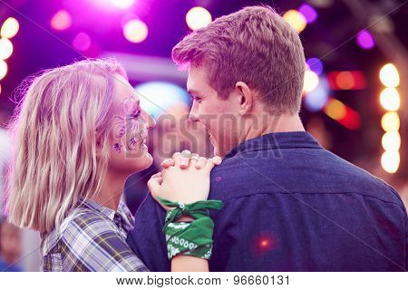 Couple looking at each other in the crowd at music festival