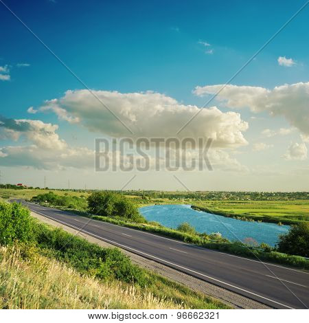 road near river under clouds in blue sky on suset