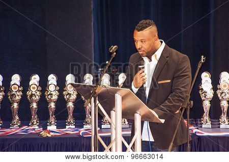 The master of the ceremony in front of the trophies of a Championship Bodybuilding and fitness