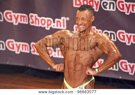 Male bodybuilder showing his best lats spread pose