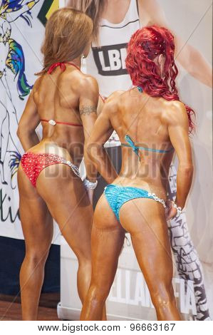Female bikini fitness models showing their best back pose
