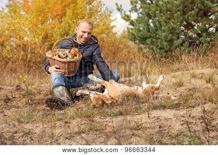Man Playing With His Dog On Autumn Forest Glade