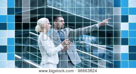 business, partnership, technology, planning and people concept - serious businessman and businesswoman with tablet pc computer over office building over blue squared grid background