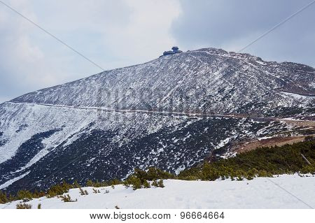 Snow-covered mountain slope and shelter