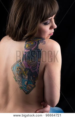 Girl, head down, tattoo owl, from back