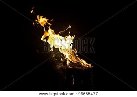 Photo of glowing log, fire by night