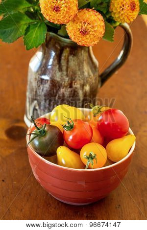 A bowl full of heritage miniature tomatoes and a vase of pompom dahlias.